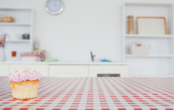 A cupcake on a tablecloth in a kitchen