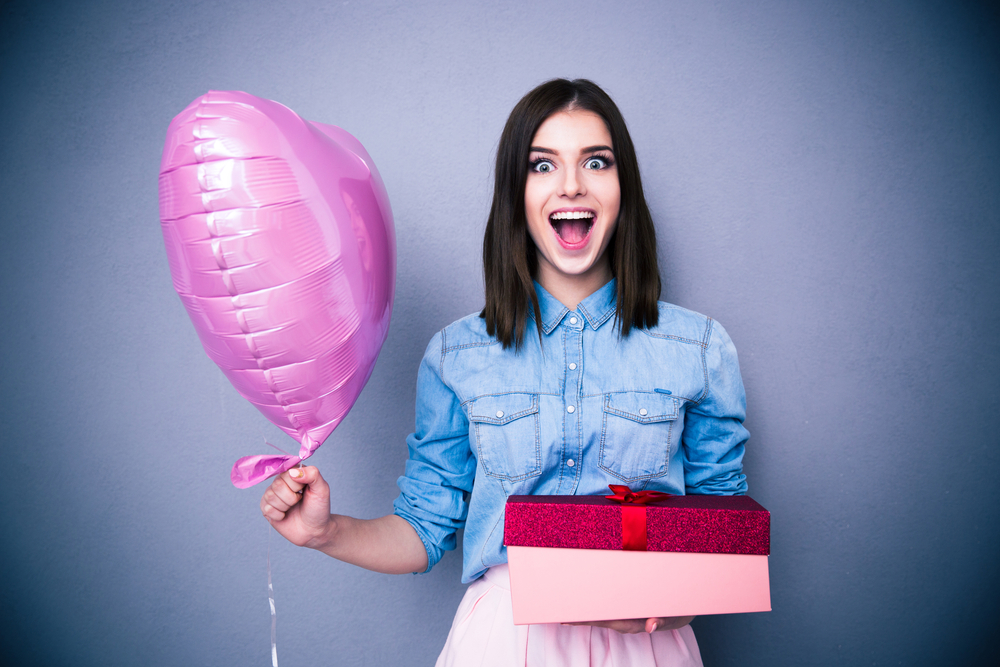 Amazed woman holding balloon and gift box over gray background. Looking at camera.
