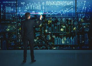 Businessman drawing business statistics on glass wall.jpeg