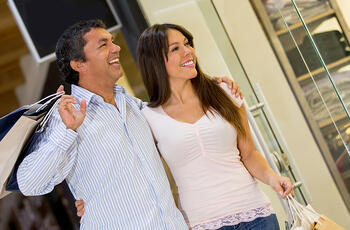 Happy couple at the shopping center looking at a window