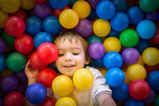 Happy cute child playing and having fun at kindergarten with colorful balls.jpeg