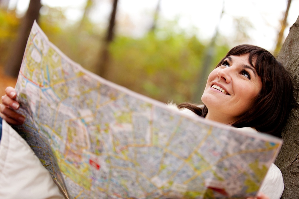 Lost female explorer holding a map outdoors