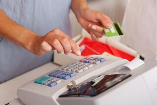 Midsection of saleswoman holding credit card while using ETR machine at boutique counter-1.jpeg