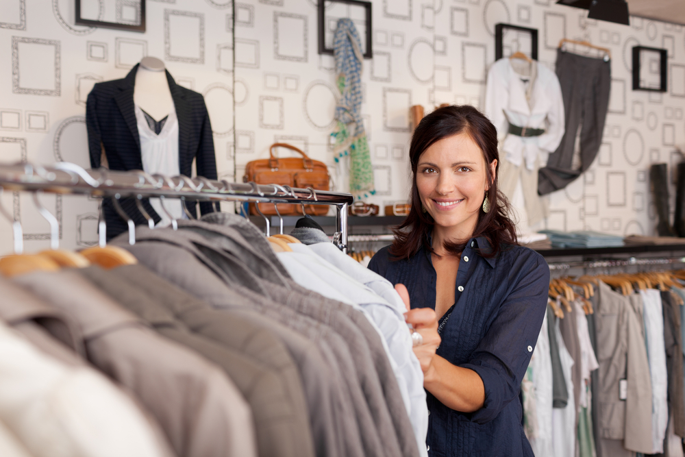 Portrait of happy female customer choosing shirt in clothing store-2