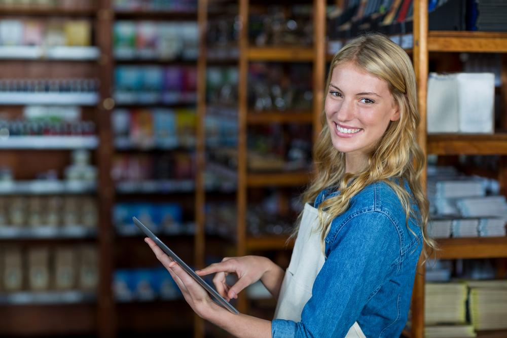 Portrait of smiling female staff using digital tablet in super market-2