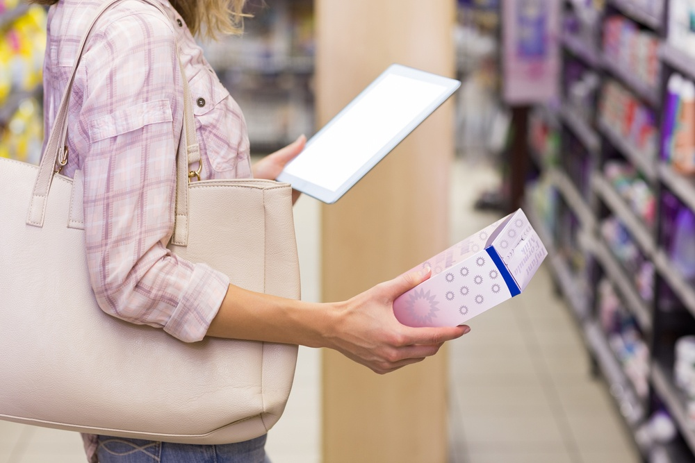 Pretty blonde woman looking at a product and using her digital tablet in supermarket