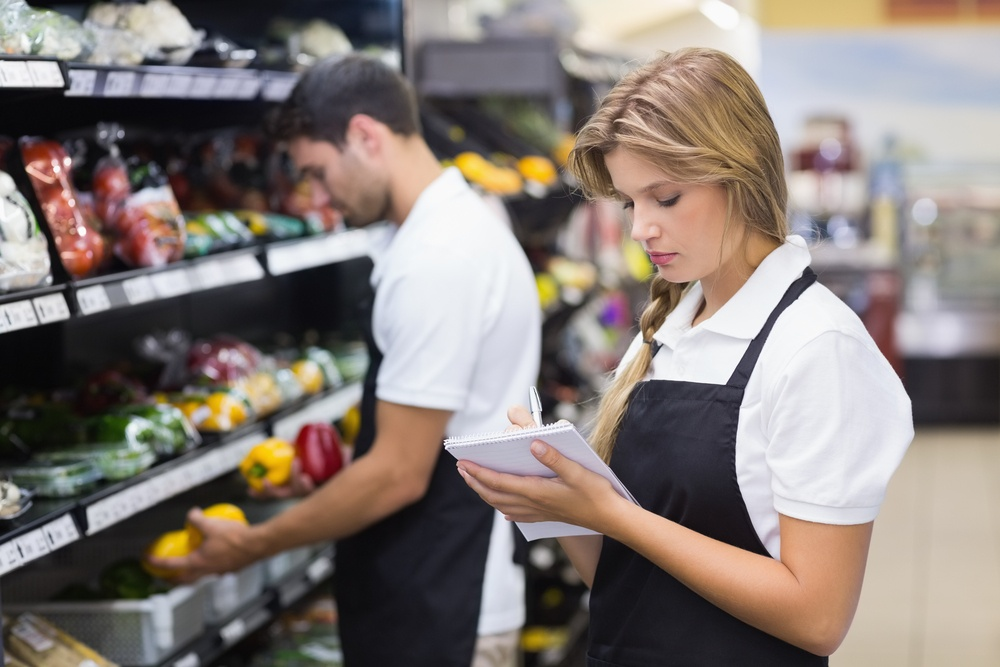 Serious staff woman writing on notepad at supermarket