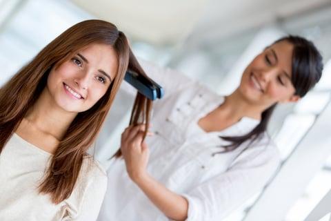 美容室で髪をセットする女性
