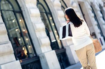 Woman walking on the street shopping and looking at windows-1
