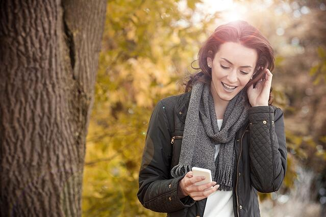 Young woman enjoying a autumn walk while texting with friends on her phone