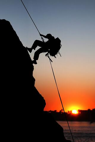 rock climber at sunset time going up a mountain.jpeg