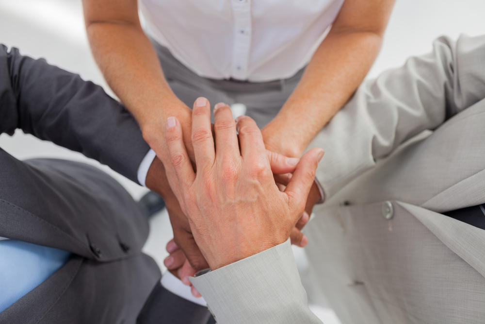 Business people gathering their hands together in the workplace