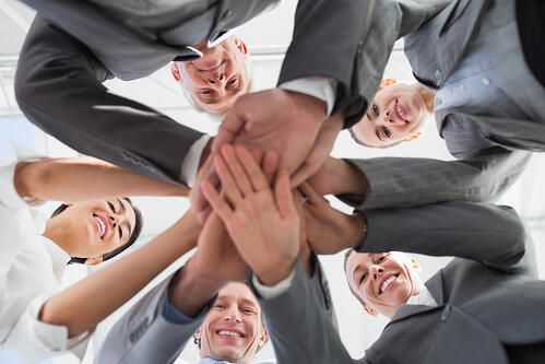 Business team standing hands together in the office