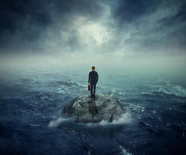 Failure crisis concept and lost business career education opportunity. Lonely young man on a rock cliff island surrounded by an ocean storm waves