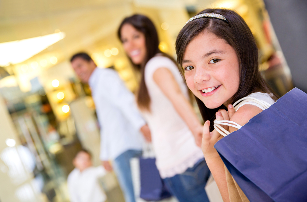 Portrait of beautiful girl smiling and shopping with her family