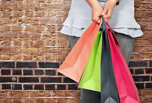 girl in bright colours holding shopping bags over a brick wall