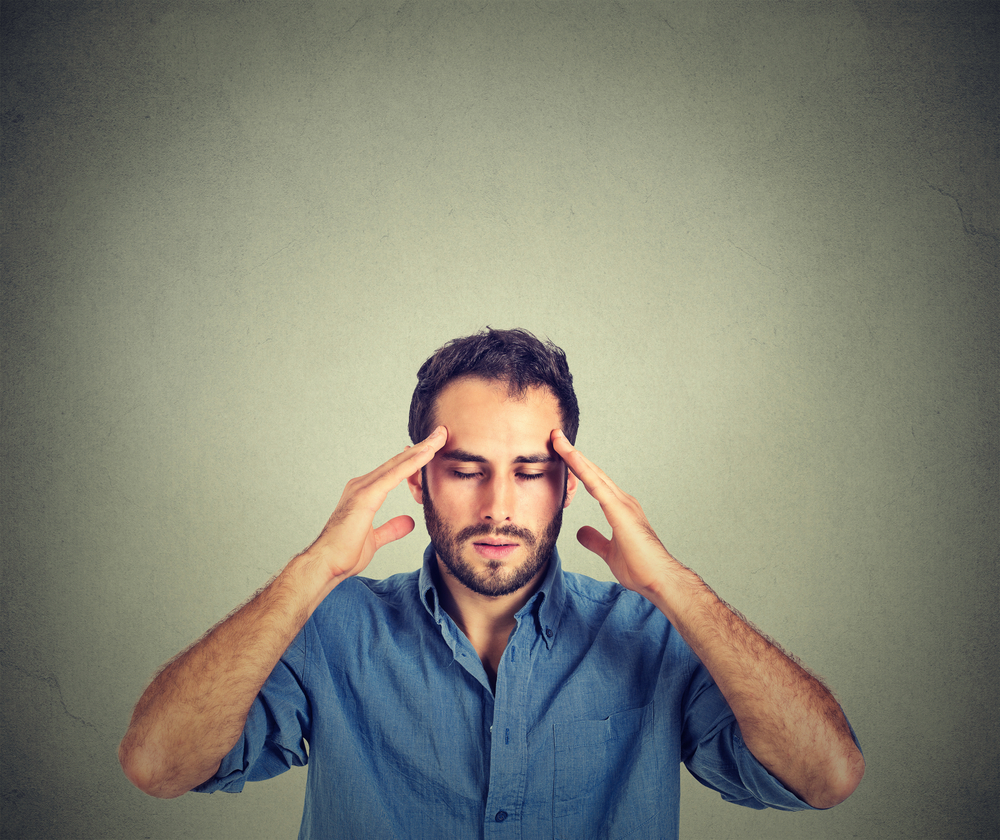 man thinking very intensely concentrating isolated on gray wall background